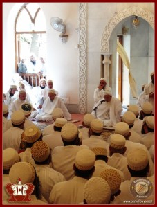 Khuzaima sitting below Syedna Mufaddal at Shz Hatim BS Sadaqallah