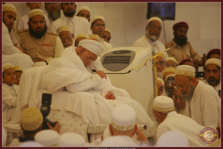 Syedna RA holding the mic with his hands and performing Nass.