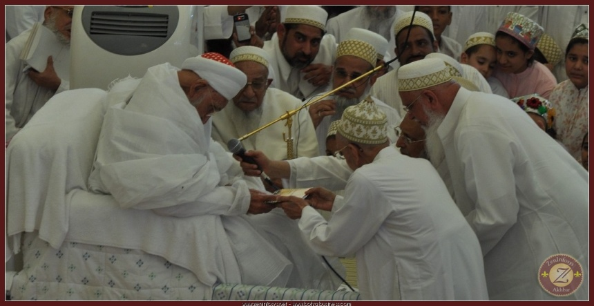 Syedna RA stretching his hands out accepting the najwa tray.